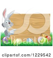Gray Bunny Pointing To A Wood Sign With Grass And Easter Eggs