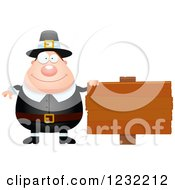 Clipart Of A Happy Male Thanksgiving Pilgrim By A Wood Sign Royalty Free Vector Illustration by Cory Thoman