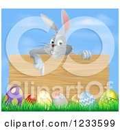 Gray Bunny Pointing Down To A Wood Sign With Grass And Easter Eggs