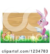Clipart Of A Pink Bunny Pointing To A Wood Sign With Grass And Easter Eggs Royalty Free Vector Illustration