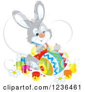 Clipart Of A Gray Male Bunny Rabbit Painting An Easter Egg In Colorful Patterns Royalty Free Vector Illustration