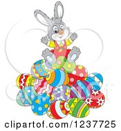 Clipart Of A Cute Cheerful Gray Easter Bunny Sitting On A Pile Of Eggs Royalty Free Vector Illustration