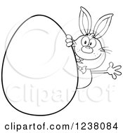 Clipart Of A Black And White Rabbit Waving Around A Giant Easter Egg Royalty Free Vector Illustration