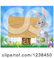 Clipart Of A Gray Bunny By A Wood Sign With A Basket Grass And Easter Eggs Royalty Free Vector Illustration by AtStockIllustration