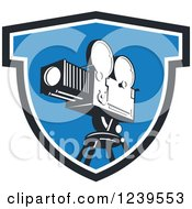 Clipart Of A Retro Movie Camera In A Blue Shield Royalty Free Vector Illustration