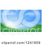 Sun Rising Over A Grassy Landscape Against A Blue Sky