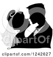 Clipart Of A Silhouetted Bride And Groom About To Kiss Royalty Free Vector Illustration