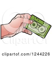 Clipart Of A Hand Holding A Green Cassette Tape Royalty Free Vector Illustration by Lal Perera
