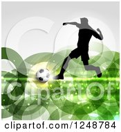 Clipart Of A 3d Soccer Ball And Silhouetted Male Player Over Green Rings Royalty Free Vector Illustration by KJ Pargeter