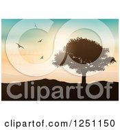 Clipart Of Birds Flying Over A Lone Tree And Hilly Landscape With Wind Turbines Royalty Free Vector Illustration by KJ Pargeter