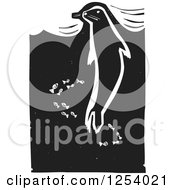 Clipart Of A Black And White Woodcut Swimming Seal And Fish Royalty Free Vector Illustration