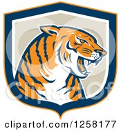Clipart Of A Retro Growling Tiger Head In A Blue Orange White And Tan Shield Royalty Free Vector Illustration