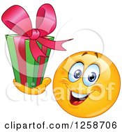Clipart Of A Yellow Smiley Emoticon Holding A Christmas Gift Royalty Free Vector Illustration by yayayoyo
