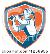 Clipart Of A Retro Male Coal Miner Swinging A Pickaxe In An Orange Blue And White Shield Royalty Free Vector Illustration