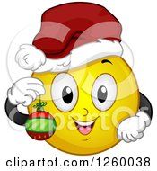 Clipart Of A Christmas Emoticon Holding A Bauble Royalty Free Vector Illustration