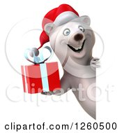 Clipart Of A 3d Christmas Polar Bear Holding A Gift Around A Sign Royalty Free Illustration