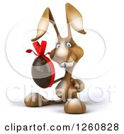 Clipart Of A 3d Brown Bunny Rabbit Holding A Chocolate Egg Royalty Free Illustration