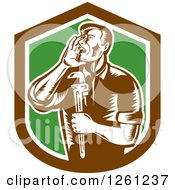 Clipart Of A Retro Woodcut Plumber Hollering And Holding A Monkey Wrench In A Brown White And Green Shield Royalty Free Vector Illustration