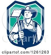 Clipart Of A Retro Male Farmer Holding A Hoe In A Blue White And Turquoise Shield Royalty Free Vector Illustration