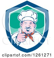 Clipart Of A Cartoon Male Chef Holding A Thumb Up In A Blue White And Green Shield Royalty Free Vector Illustration
