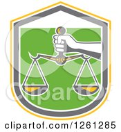 Clipart Of A Hand Holding Scales Of Justice In A Yellow White Gray And Green Shield Royalty Free Vector Illustration