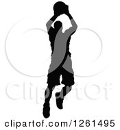 Clipart Of A Black Silhouetted Basketball Player In Action Royalty Free Vector Illustration