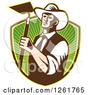 Clipart Of A Retro Woodcut Cowboy Farmer Holding A Hoe Over A Shield Of Green Rays Royalty Free Vector Illustration