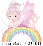 Clipart Of A Happy Pink Fairy Pixie Girl Resting On A Rainbow Royalty Free Vector Illustration