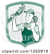 Clipart Of A Retro Cartoon Male Plumber Holding A Monkey Wrench And Taking A Call In A Green Shield Royalty Free Vector Illustration by patrimonio