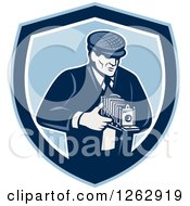 Clipart Of A Retro Male Photographer Using A Bellows Camera In A Blue And White Shield Royalty Free Vector Illustration