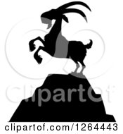 Clipart Of A Black Silhouetted Rearing Buck Goat On A Mountain Top Royalty Free Vector Illustration by Hit Toon