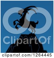 Clipart Of A Silhouetted Rearing Rearing Buck Goat On A Mountain Peak Over Blue Royalty Free Vector Illustration
