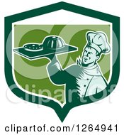Clipart Of A Retro Woodcut Male Chef Holding Gelatin Or Cake On A Platter In A Green And White Shield Royalty Free Vector Illustration