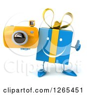 Clipart Of A 3d Blue Gift Character Holding A Camera And Thumb Up Royalty Free Illustration
