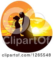 Silhouetted Wedding Couple Kissing In A Sunset Heart