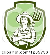 Clipart Of A Retro Female Farmer Holding A Pitchfork In A Green And White Shield Royalty Free Vector Illustration by patrimonio