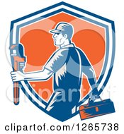 Clipart Of A Retro Woodcut Male Plumber Carrying A Monkey Wrench And Tool Box In A Blue White And Orange Shield Royalty Free Vector Illustration