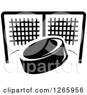Clipart Of A Black And White Hockey Puck And Net Royalty Free Vector Illustration by Vector Tradition SM