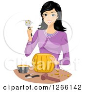 Clipart Of A Young Asian Woman Carving A Halloween Pumpkin Royalty Free Vector Illustration