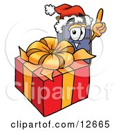 Clipart Picture Of A Suitcase Cartoon Character Standing By A Christmas Present