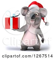 Clipart Of A 3d Christmas Koala Holding A Red Present Gift Box Royalty Free Illustration