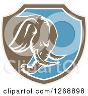 Clipart Of A Retro Woodcut Charging Elephant In A Taupe Brown White And Blue Shield Royalty Free Vector Illustration