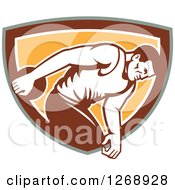 Clipart Of A Retro Male Discus Thrower In An Orange Brown White And Green Shield Royalty Free Vector Illustration