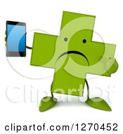 Clipart Of A 3d Unhappy Green Pharmaceutical Cross Character Holding Aand Pointing To A Smart Phone Royalty Free Illustration