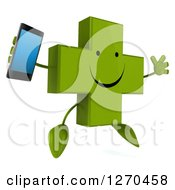 Clipart Of A 3d Happy Green Pharmaceutical Cross Character Jumping Facing Right And Holding A Smart Phone Royalty Free Illustration