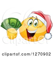 Clipart Of A Happy Emoticon Smiley Wearing A Christmas Santa Hat And Holding Cash Money Royalty Free Vector Illustration