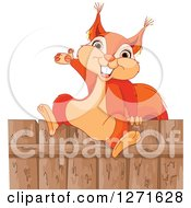 Clipart Of A Cute Happy Squirrel Presenting And Sitting On A Wood Fence Royalty Free Vector Illustration