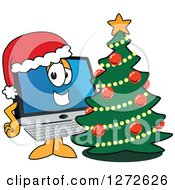 Clipart Of A Happy PC Computer Mascot Wearing A Santa Hat By A Christmas Tree Royalty Free Vector Illustration