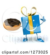 Clipart Of A 3d Happy Blue Gift Character Holding Up A Finger And A Chocolate Frosted Cupcake Royalty Free Illustration by Julos