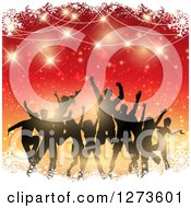 Clipart Of A Silhouetted Group Of People Dancing At A Christmas Party Over Gradient Red And Orange With Snow And Flares Royalty Free Vector Illustration
